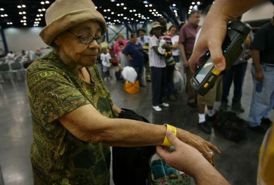 Minnie Thompson, 80, of Webster, waited since 9 a.m. to be evacuated from the George R. Brown Convention Center and is finally scanned to board a bus bound for Mesquite on Thursday. Photo: MAYRA BELTRÁN, CHRONICLE