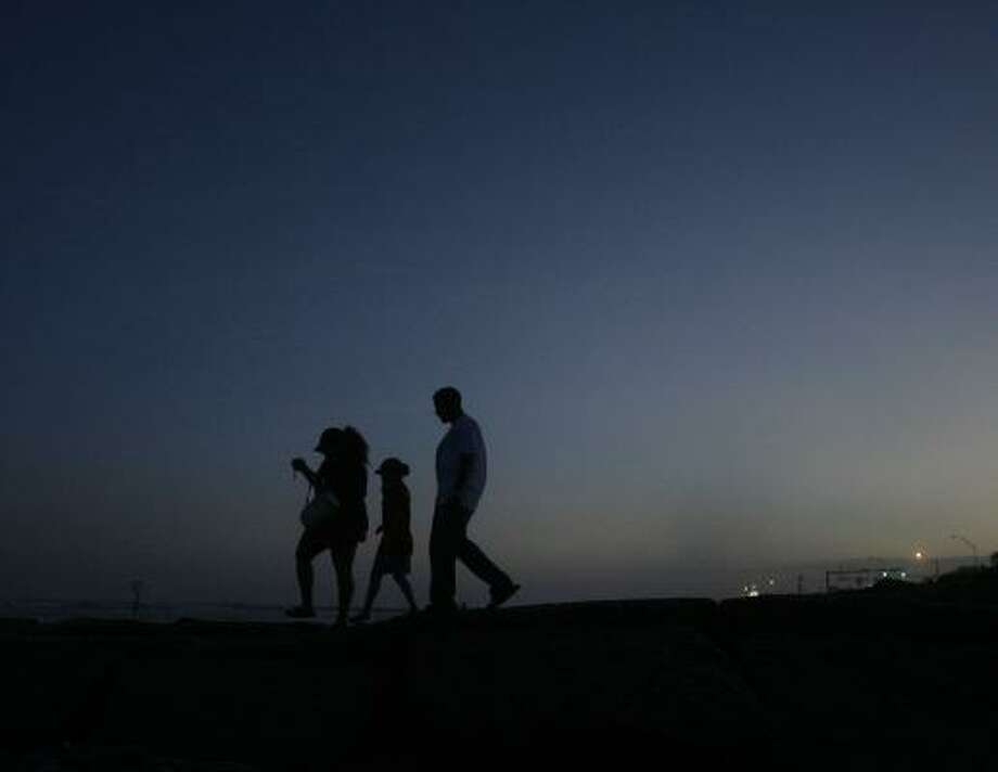 WENDY Yanes, left, Diana Melendez, and Chance Weatherly walk along a jetty after sunset Thursday in Galveston. Photo: MATT SLOCUM, ASSOCIATED PRESS
