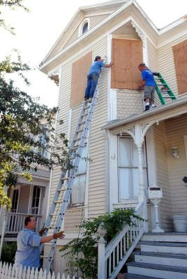 Rusty Legg, left, holds the ladder for John Moore as Chris Robertson boards up the window on Legg's 1895 home Sept. 11 in Galveston. Legg plans to stay and ride out the storm in his home. Photo: Kim Christensen, AP