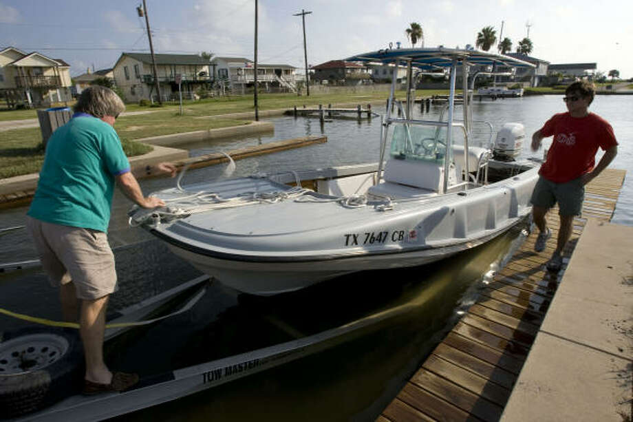 "Mark Stamey (left) and his son, Elliot (right) of Houston, pull out their boat at a boat dock in Jamacia Beach in preparation for Hurricane Ike on Sept. 10.  ""We are going to bring it up to Houston,"" Mark Stamey said. ""You don't want to take any chances."" Photo: Johnny Hanson, Chronicle"