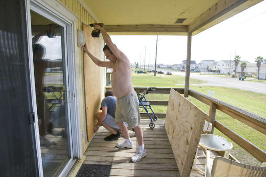 Michael Collins, foreground, and his brother Stephen board up their father's retirement home in western Galveston. Photo: Nick De La Torre, CHRONICLE