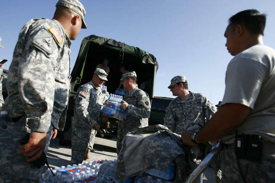 Army National Guard soldiers load water onto a truck during staging in preparation for Ike in Housto