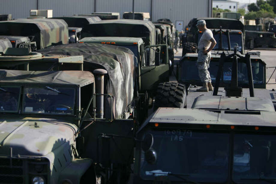 An Army National Guard soldier stands on one of the 50 to 60 trucks being gathered Sept. 10 in Houston for a response to Hurricane Ike. Photo: Sharon Steinmann, Chronicle