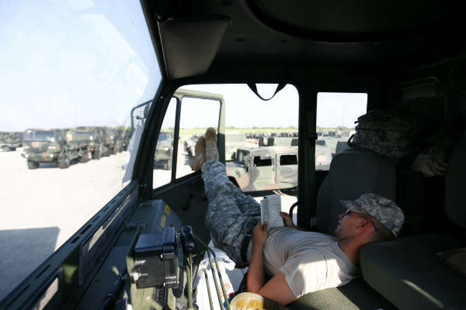 Specialist Jeffrey Hicks reads in his truck Sept. 10  in Houston where the National Guard is staging vehicles for a response to Hurricane Ike. Photo: Sharon Steinmann, Chronicle