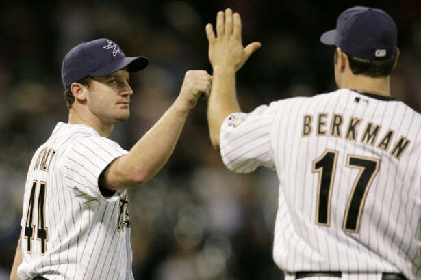 Roy Oswalt is congratulated by Lance Berkman after defeating the Pirates.