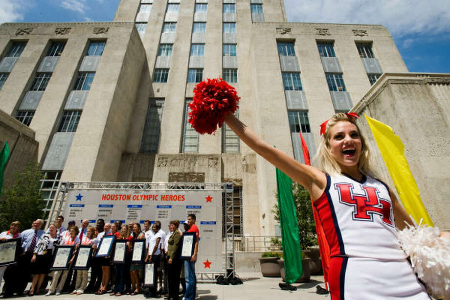 A University of Houston cheerleader entertains the crowd as a group of Houston Olympians pose for a group photo during the Houston Olympic Heroes Day at City Hall on Tuesday. Photo: Smiley N. Pool, Chronicle
