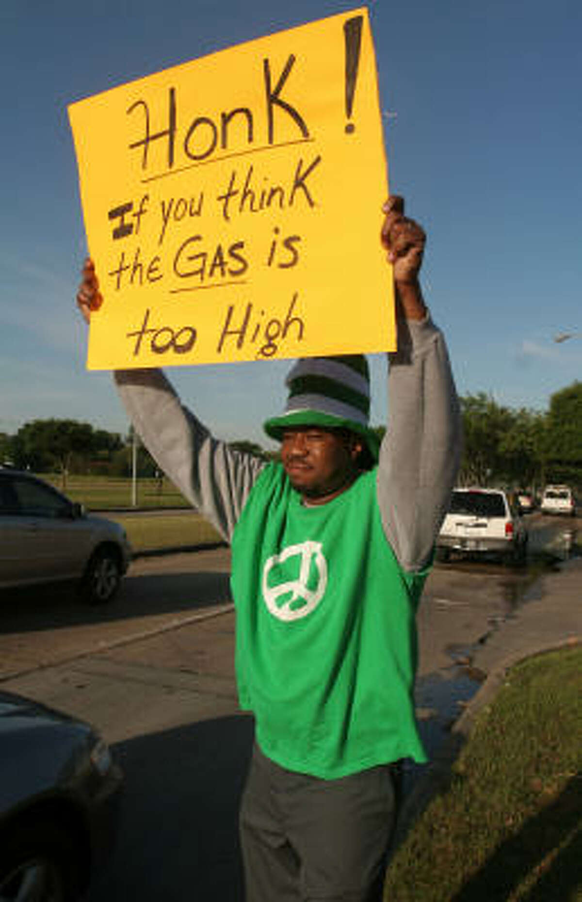 Despite drivers' increasing demand for fuel, Dylan Parker protests high gas prices outside a gas station on North Braeswood.