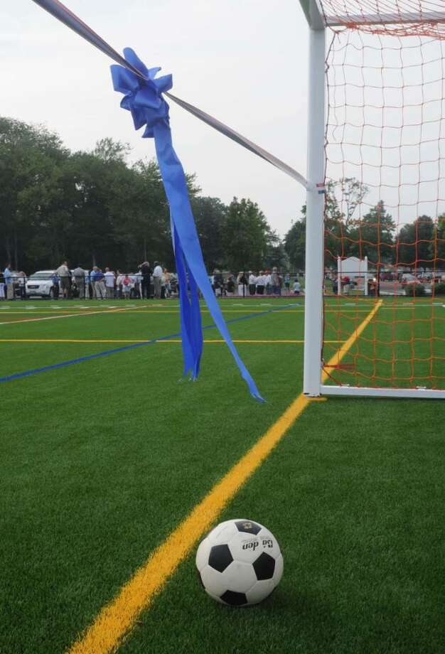 The ceremonial ribbon and soccer ball wait as the dedication ceremony takes place in the background. The John Perry Memorial Field was dedicated on Wednesday  at Rogers Park in Danbury. Photo:                           Jay Weir          , Jay Weir