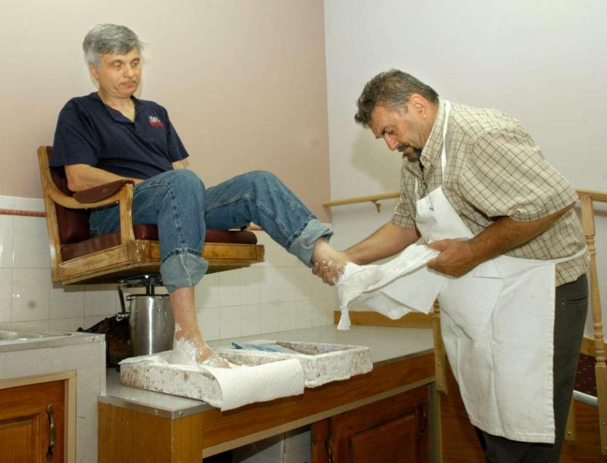 Carol Kaliff/staff photographer. Joe Grana of Danbury left has a mold made of his feet by Alvaro Moniz who is making orthotics for him. Moniz has run Alvaro's Orthopedic Footwear & Shoe Service South St. Danbury since 1973.
