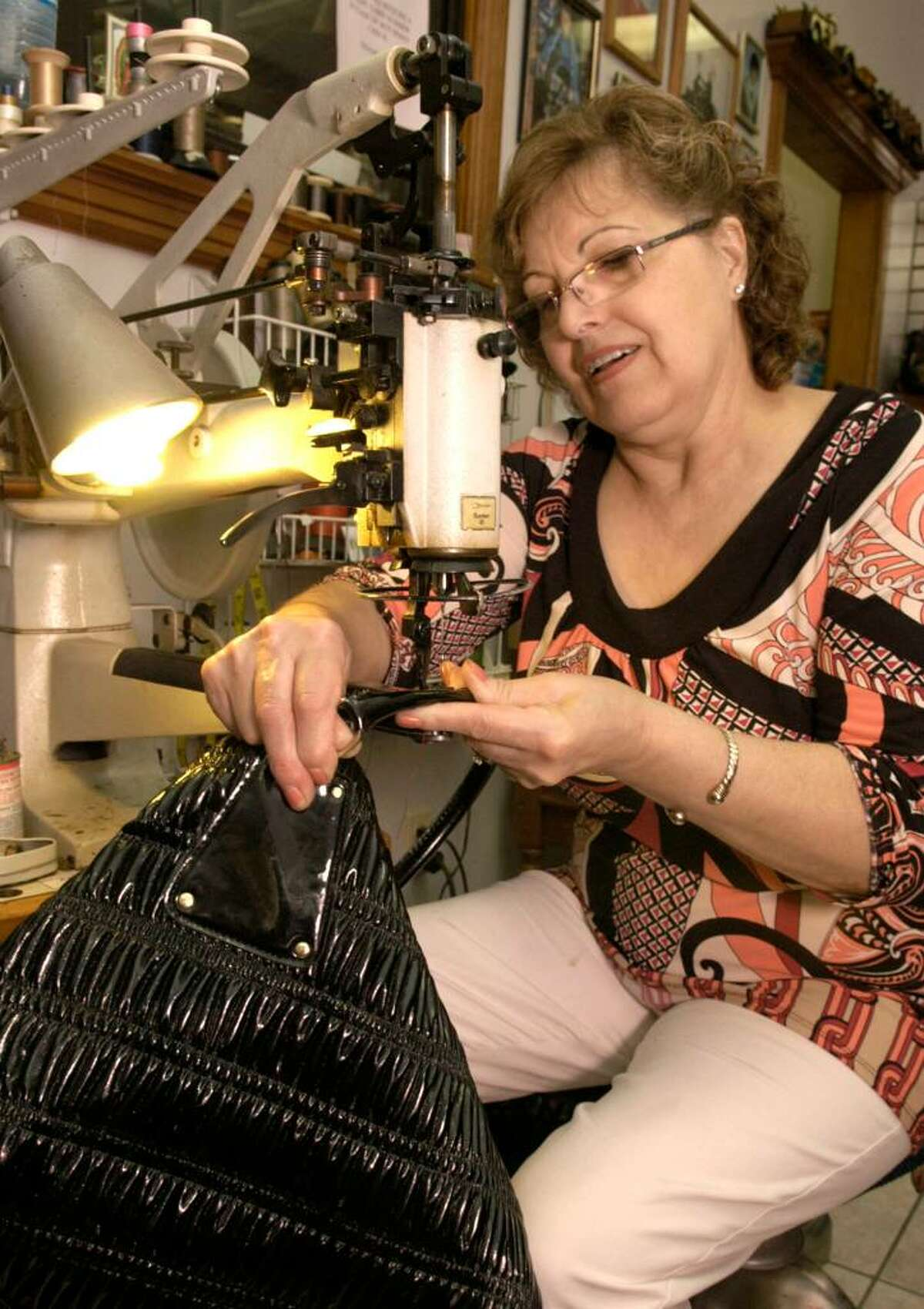 Carol Kaliff/staff photographer. Herminia Moniz has worked with her husband Alvaro since 1986 in their custum shoe and repair business. She runs the counter and does stitching, a skill she learned from her mother. Photo taken August 5, 2009