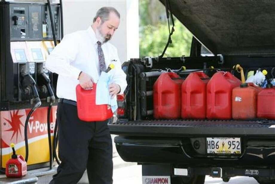 John McDonnell, de  Biloxi, Misouri, se prepara acumulando gasolina el miércoles 27 de agosto del 2008 ante la llegada de la tormenta Gustav. Photo: JOHN FITZHUGH, AP