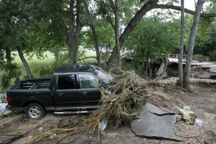 A washed out truck and bridge are shown today after a  storm flooded homes, closed roads, and carried cars away in Marble Falls. Photo: Matt Slocum, AP