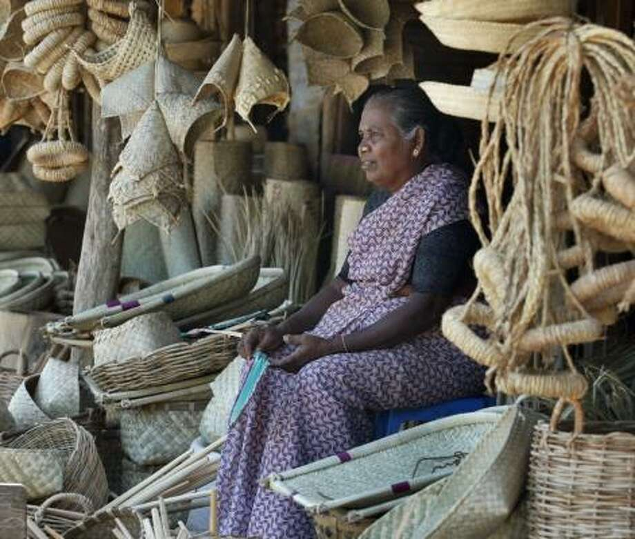Palani Amma Subramaniyam sits surrounded by woven baskets and terra cotta pots in her deserted market stall in the rebel-controlled town of Kilinochchi, Sri Lanka. Photo: GEMUNU AMARSINGHE, AP