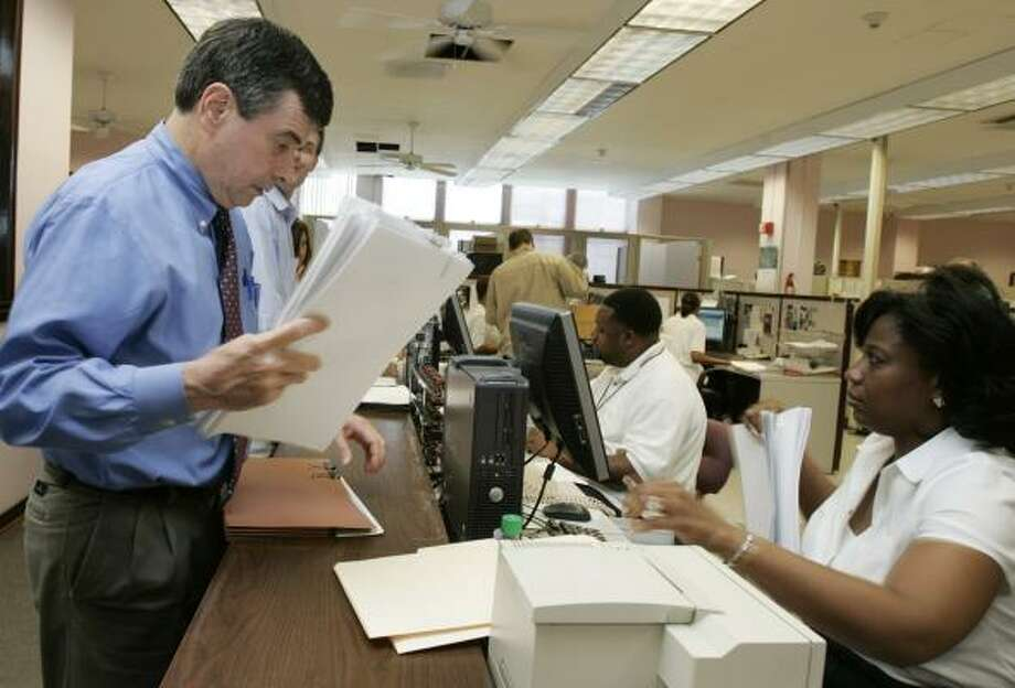 New Orleans attorney Wiley Lastrapes Jr. files documents with Shalahn Campbell, deputy clerk of the Orleans Civil District Court, on Thursday. Inundated courts are bracing for a last-minute wave of lawsuits over damage from Hurricane Katrina. Photo: BILL HABER, ASSOCIATED PRESS