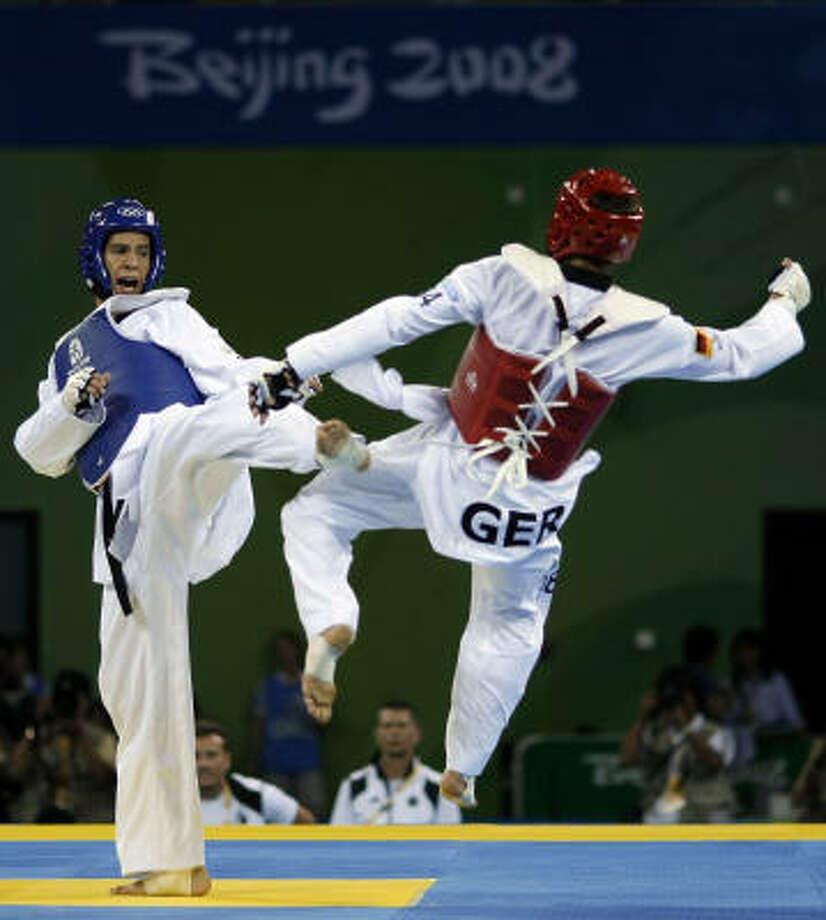 Mark López (izq.) golpea con una patada al alemán Daniel Manz en un combate de los cuartos de final de la categoría de 68 kilos del taekwondo olímpico en los Juegos de Beijing. Photo: Matt Dunham, AP