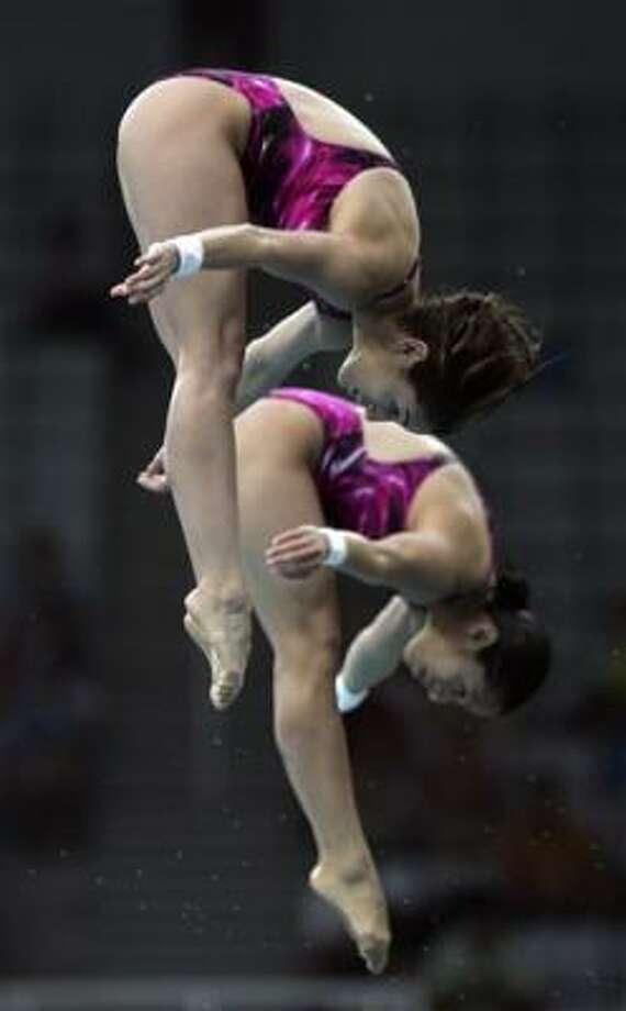 Las mexicanas Paola Espinosa (arriba) y Tatiana Ortiz en acción al ganar la medalla olímpica  de bronce de los saltos sincronizados desde plataforma de 10 metros. Photo: Domenico Stinellis, AP