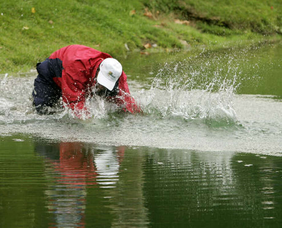 Woody Austin falls into the lake after hitting out of the water on the 14th hole. Photo: TIMOTHY A. CLARY, AFP/Getty Images