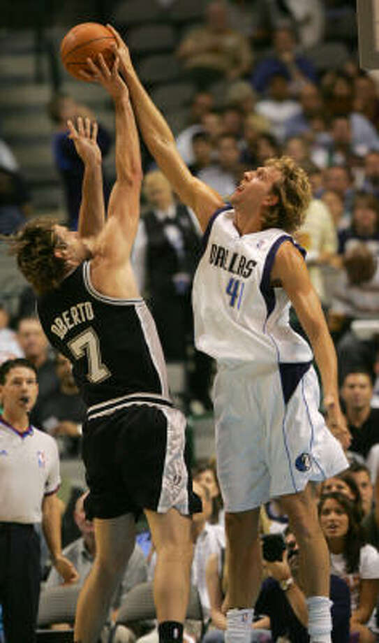 The Mavericks Dirk Nowitzki, right, blocks the shot of San Antonio's Fabricio Oberto in the first half of the preaseason opener for both teams. Photo: Jeffery Washington, MCT