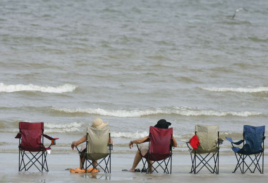 Vacationers relas on the beach in Surfside. Photo: James Nielsen, Houston Chronicle
