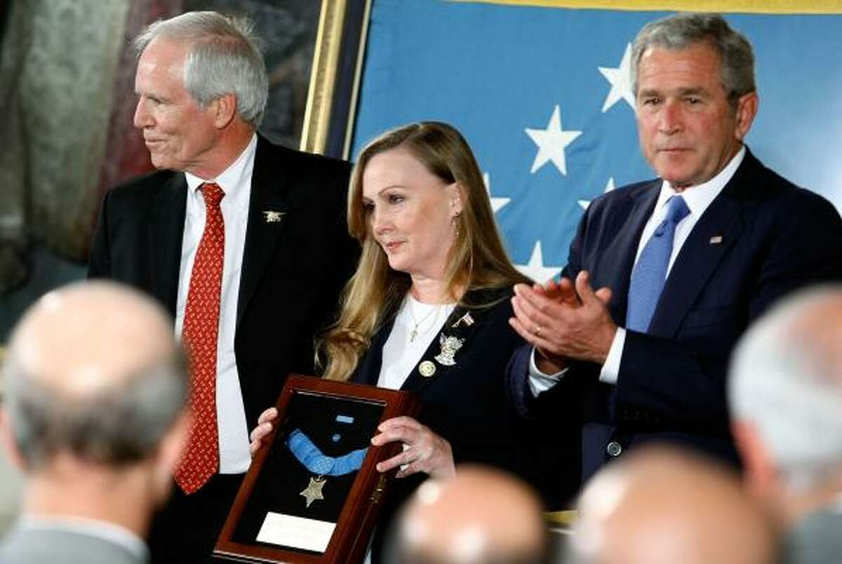 """President Bush presents the Medal of Honor at a White House ceremony Monday to Daniel and Maureen Murphy, parents of Navy SEAL Lt. Michael Murphy, for acting """"with complete disregard for his own life."""" Murphy died in a June 2005 battle with Taliban fighters."""