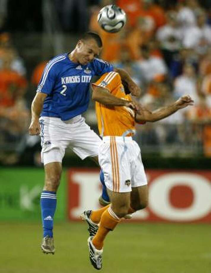 Kansas City's Michael Harrington, left, appears to have taken a damaging swipe at Dynamo defender Brian Mullan. Photo: BILLY SMITH II, CHRONICLE