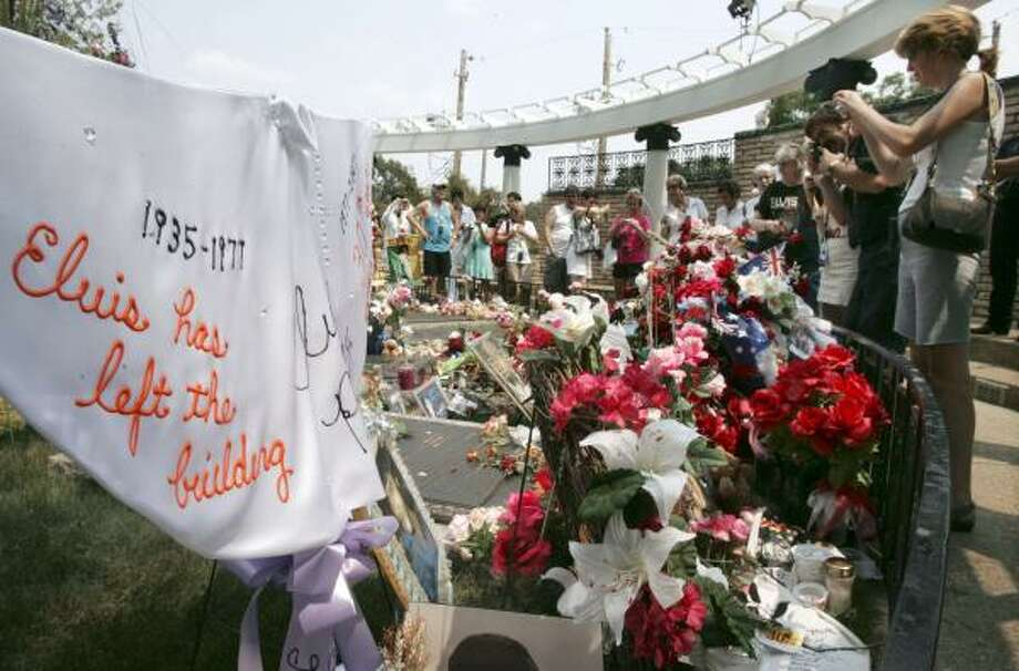 The grave of Elvis Presley is decorated with flowers and items made by fans on the grounds of Graceland in Memphis, Tenn., on the 30th anniversary of Presley's death Aug. 16, 2007. Photo: Mark Humphrey, AP