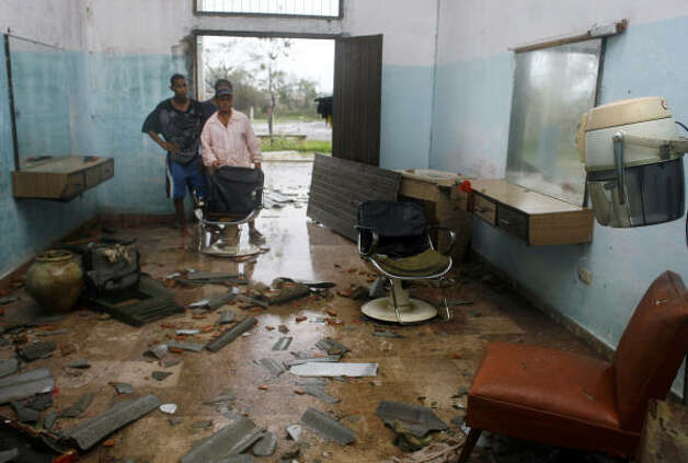 Men look inside a barber shop destroyed by Hurricane Gustav in Paso Real, Cuba, on Sunday. Photo: Javier Galeano, Associated Press