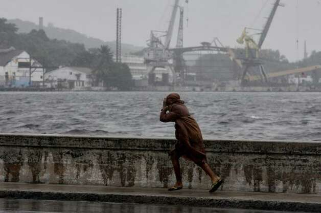 A resident runs for cover from rains caused by Hurricane Gustav in Havana. Photo: Javier Galeano, Associated Press