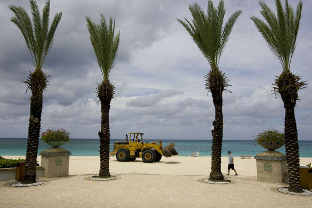 A bulldozer passes on the beach in front of a Cayman Island seaside resort as good weather held even as the Gustav was expected later in the day Friday. Photo: Brennan Linsley, AP