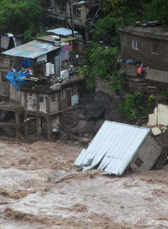 A home is seen fallen into a swollen river caused by  Gustav in Kingston, Jamaica Friday. Photo: Collin Reid, AP