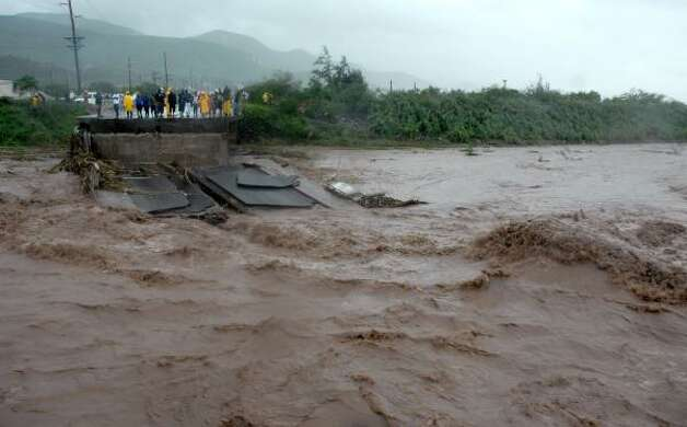 Residents watch a bridge that collapsed due to heavy rains caused by Tropical Storm Gustav in Kingston, Jamaica Friday. Photo: Collin Reid, AP