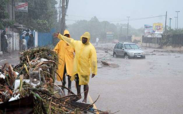 Residents walk along a flooded street following heavy rains caused by Tropical Storm Gustav in Kingston Friday. Photo: Collin Reid, AP