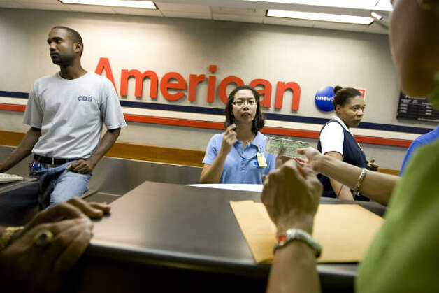 The check-in counter at American Airlines in George Town, Grand Cayman, was busy at dawn Friday with people trying to leave the island. Photo: Brennan Linsley, AP