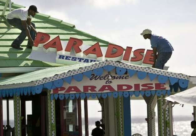 Workers remove a roof sign from Paradise Restaurant in preparation for the arrival of Gustav in George Town on Grand Cayman Island on Thursday. Photo: Brennan Linsley, Associated Press