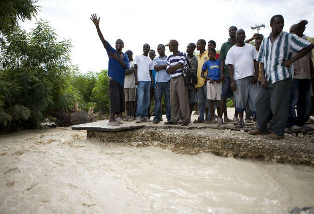 People wait at one side of a road cut off by flooding caused by Tropical Storm Gustav in Malpasse, Haiti. Photo: Ariana Cubillos, Associated Press