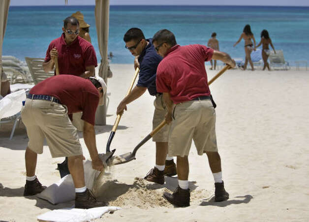 Workers at a seaside resort fill sandbags in preparation for Gustav as tourists walk along the shores of Seven Mile Beach on Grand Cayman Island Thursday. Photo: Brennan Linsley, AP