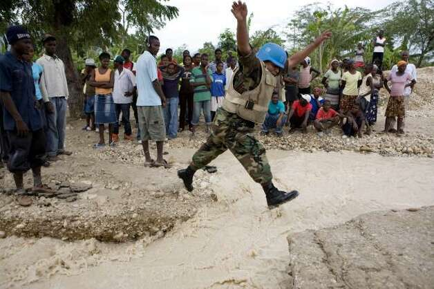 A Peruvian U.N. peacekeeper jumps over flood waters caused by heavy rain brought by Tropical Storm Gustav in Malpasse, Haiti, Thursday. Photo: Ariana Cubillos, AP