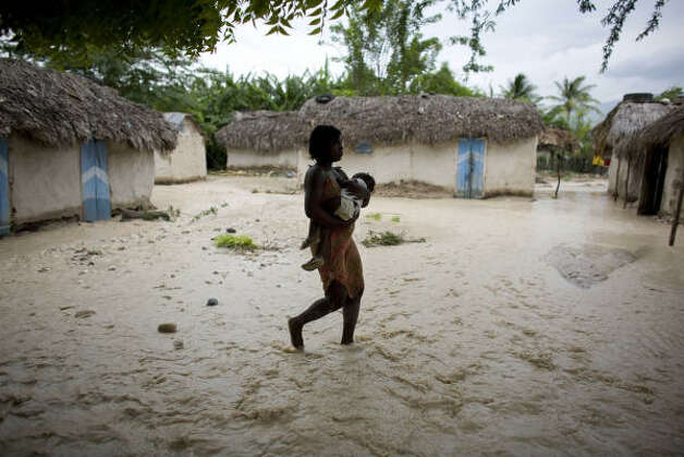 A woman carries a child through flooded roads caused by Gustav in Fond Parisien village, Haiti, Thursday. Photo: Ariana Cubillos, AP