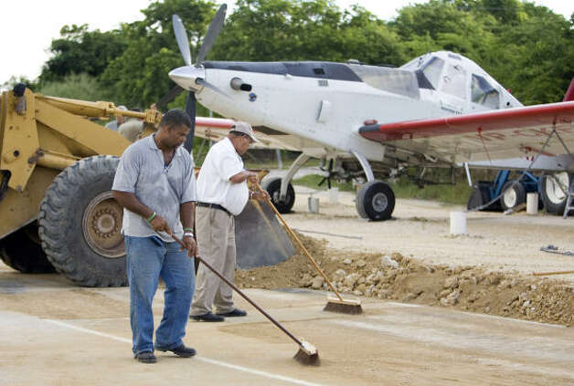 Workers prepare an area where small planes will be tied down Thursday in the Cayman Islands in preparation for Gustav. Photo: Brennan Linsley, AP