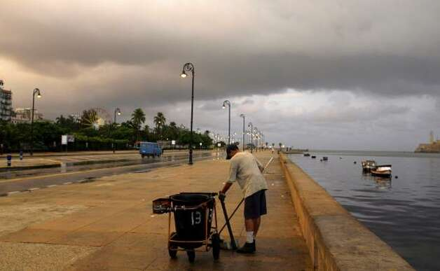A worker sweeps Havana's seafront, known as the Malecon, after rains, Thursday in Cuba. Photo: Javier Galeano, AP