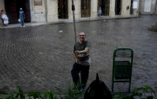 A man cleans a window after rains in Havana, Cuba, Thursday. Photo: Javier Galeano, AP