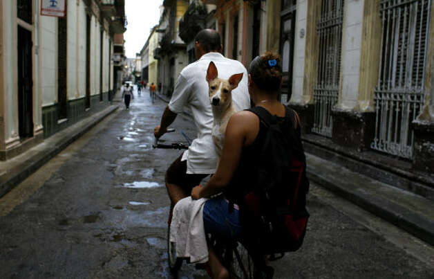 A couple rides a bicycle with a dog after rains in Havana Thursday. Photo: Javier Galeano, AP