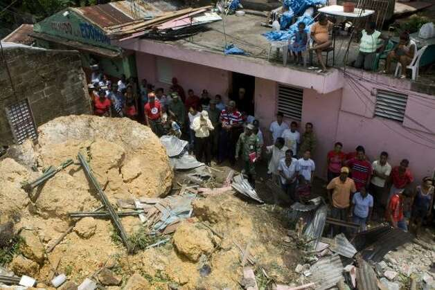 Residents look at several houses destroyed by a landslide in Guachupita, Santo Domingo. Photo: Ramon Espinosa, AP