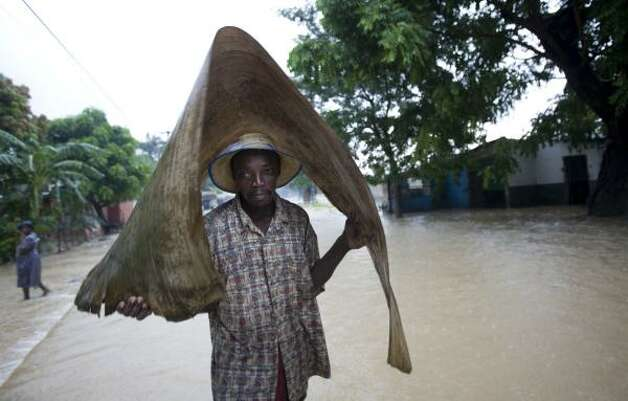 A man covers himself with a dry palm leave as he  walks through a flooded street during heavy rains caused by Hurricane Gustav in Leogane, southern Haiti, on Aug. 27 Photo: Ariana Cubillos, AP