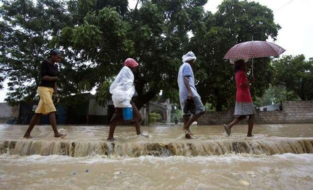 People walk through a flooded street during heavy rains caused by Hurricane Gustav in Leogan, southern Haiti, on Aug. 27. Photo: Ariana Cubillos, AP