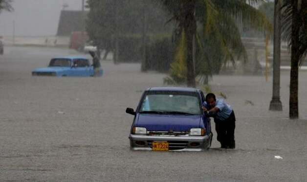 A man pushes his car through a  flooded street during heavy rains caused by the approaching Gustav  in Havana Aug. 26. Photo: Javier Galeano, AP
