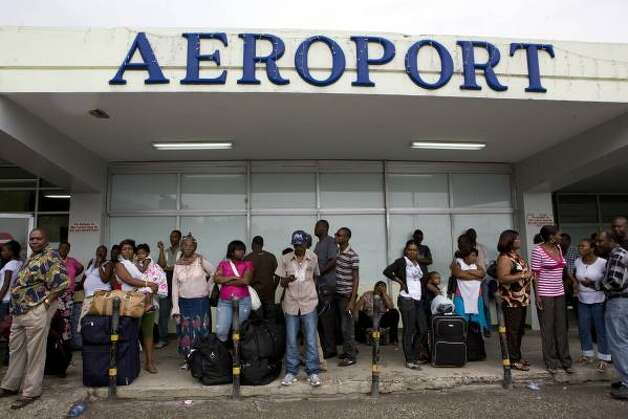 People stand in front of the international airport after all flights, in and out, were canceled due to Hurricane Gustav in Port-au-Prince Aug. 26. Photo: Ariana Cubillos, AP