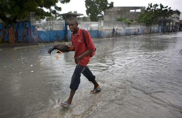 A man carrying a rooster walks through a flooded street during heavy rains caused by Hurricane Gustav in Port-au-Prince Aug. 26. Photo: Ariana Cubillos, AP