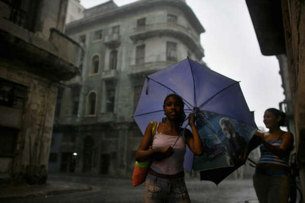 Women cover themselves with umbrellas during heavy rains caused by the approaching Hurricane Gustav in Havana, Cuba, Aug. 26. Photo: Javier Galeano, AP