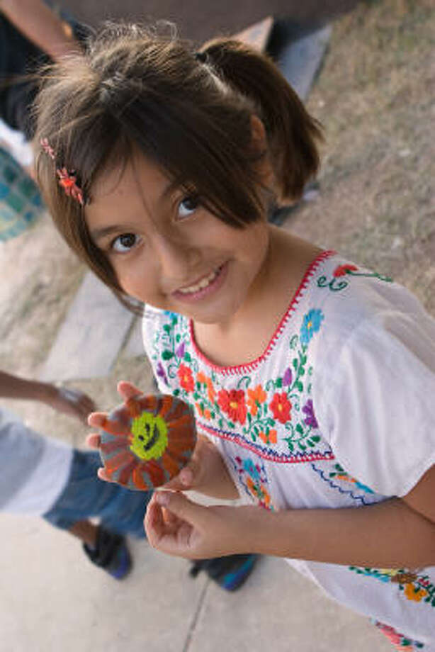 Citlali Reyes, 8, shows a stone she painted during the Day of the Dead Festival at MECA, 1900 Kane, on Oct. 28. Photo: R. Clayton McKee, For The Chronicle